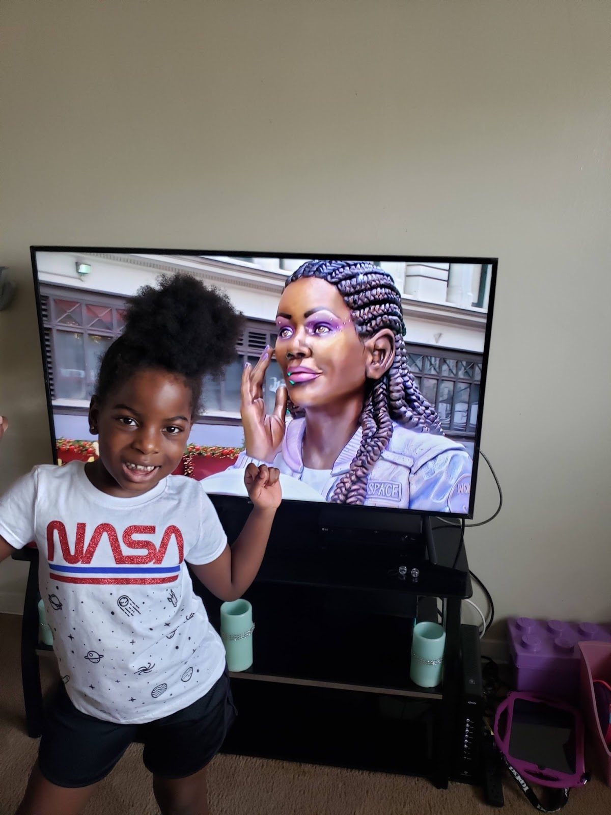 Ryan wearing a NASA shirt in front of a TV with a Black woman on the screen.