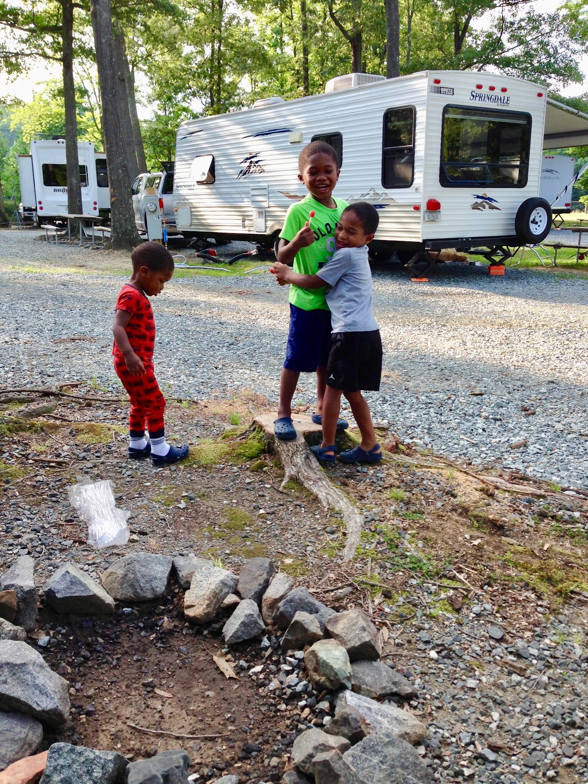 Three young boys laugh and hug at campground with travel trailers in the background