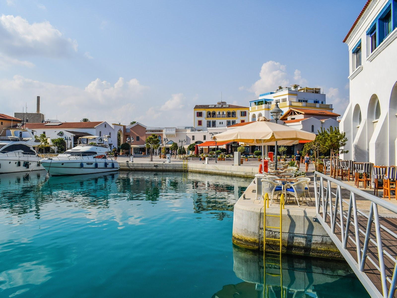 limassol marina, harbor, beautiful port with blue water, parked luxury yachts and a waterfront restaurant with outdoor seating under an umbrella. colorful buildings in the distance.