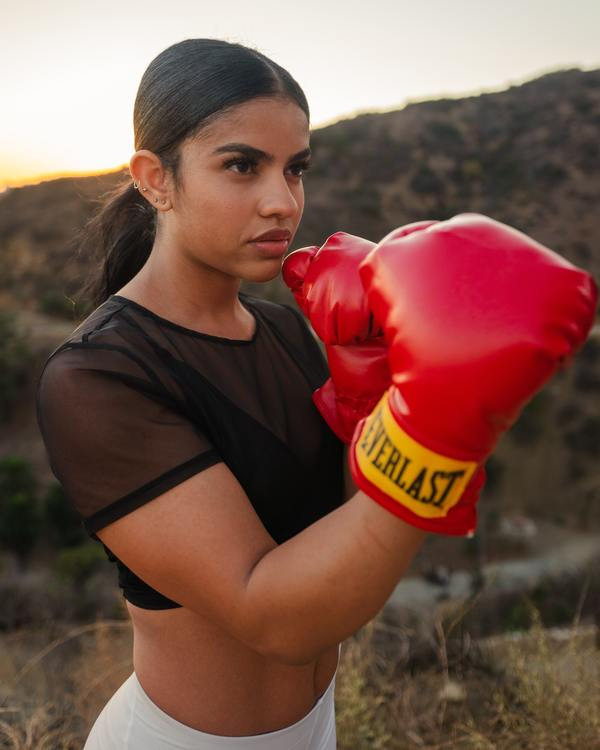 foto de uma mulher em um campo aberto com luvas de boxe
