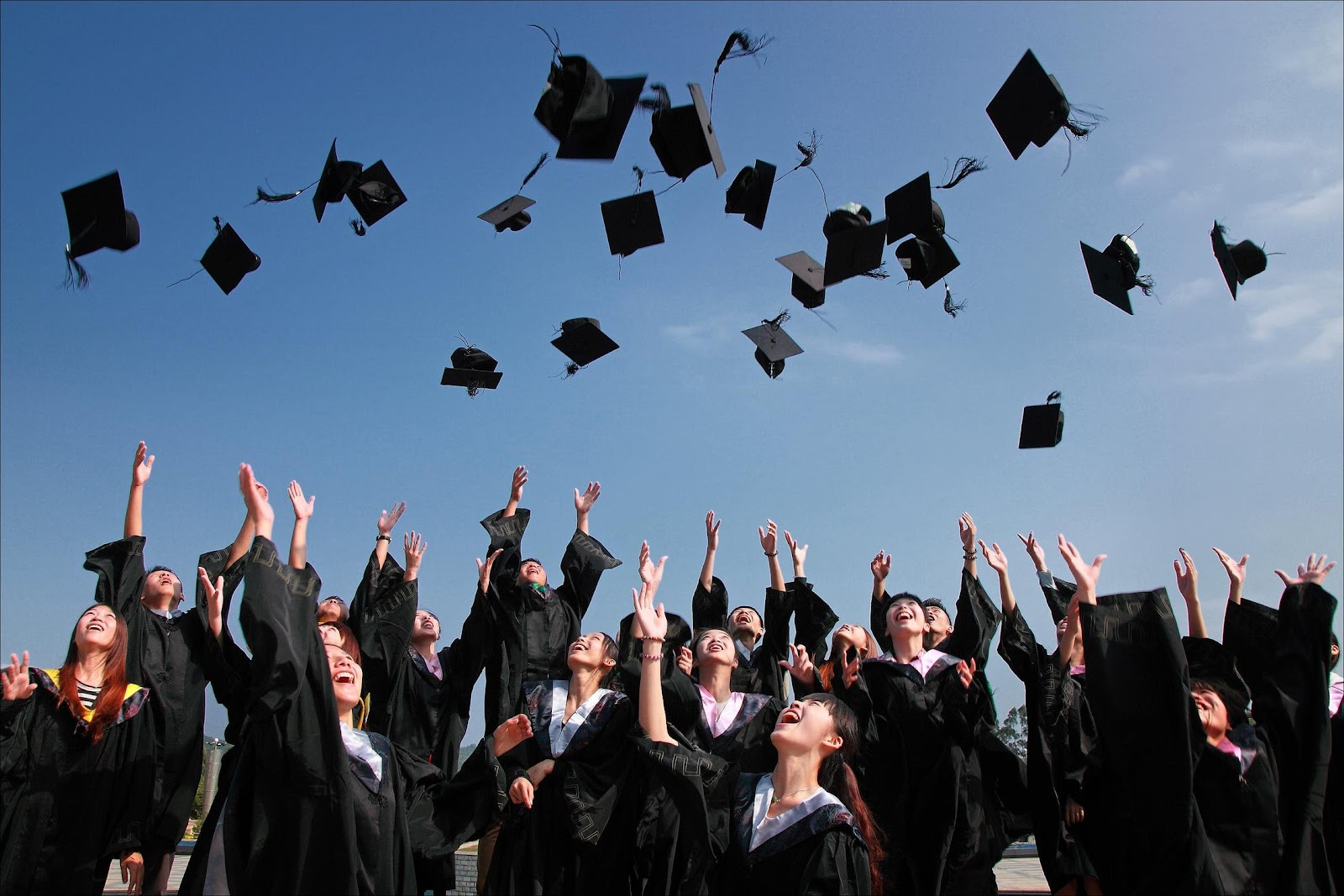 Students wearing graduation gowns throwing their caps in the air