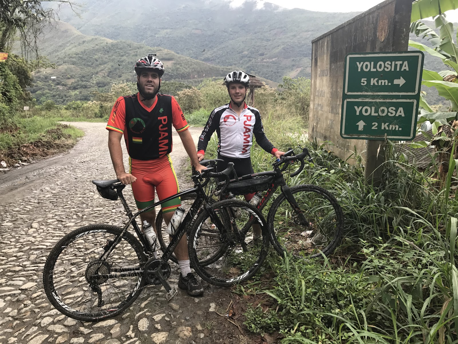 2 cyclists with bikes stopped at sign on Yungas Road