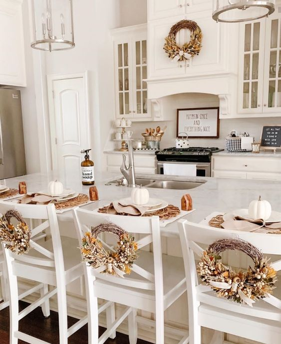 all white kitchen with fall decor wreaths on the back of the chairs and white pumpkins on the table.