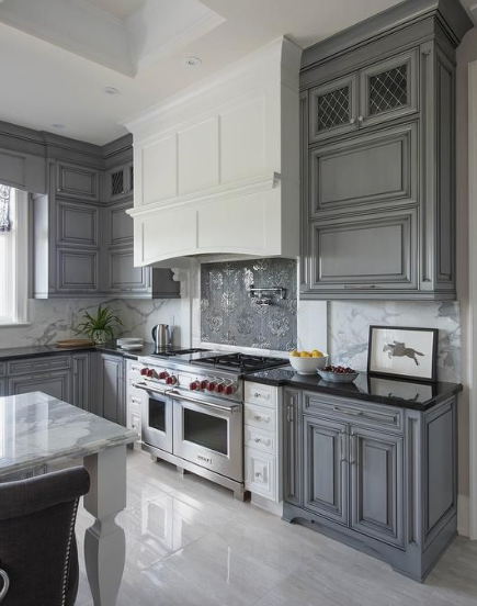 grey and white antique cabinets contrast eachother in this elegant traditional kitchen. black countertops and light grey marble floors match the cabinets and give the space a glossy finish
