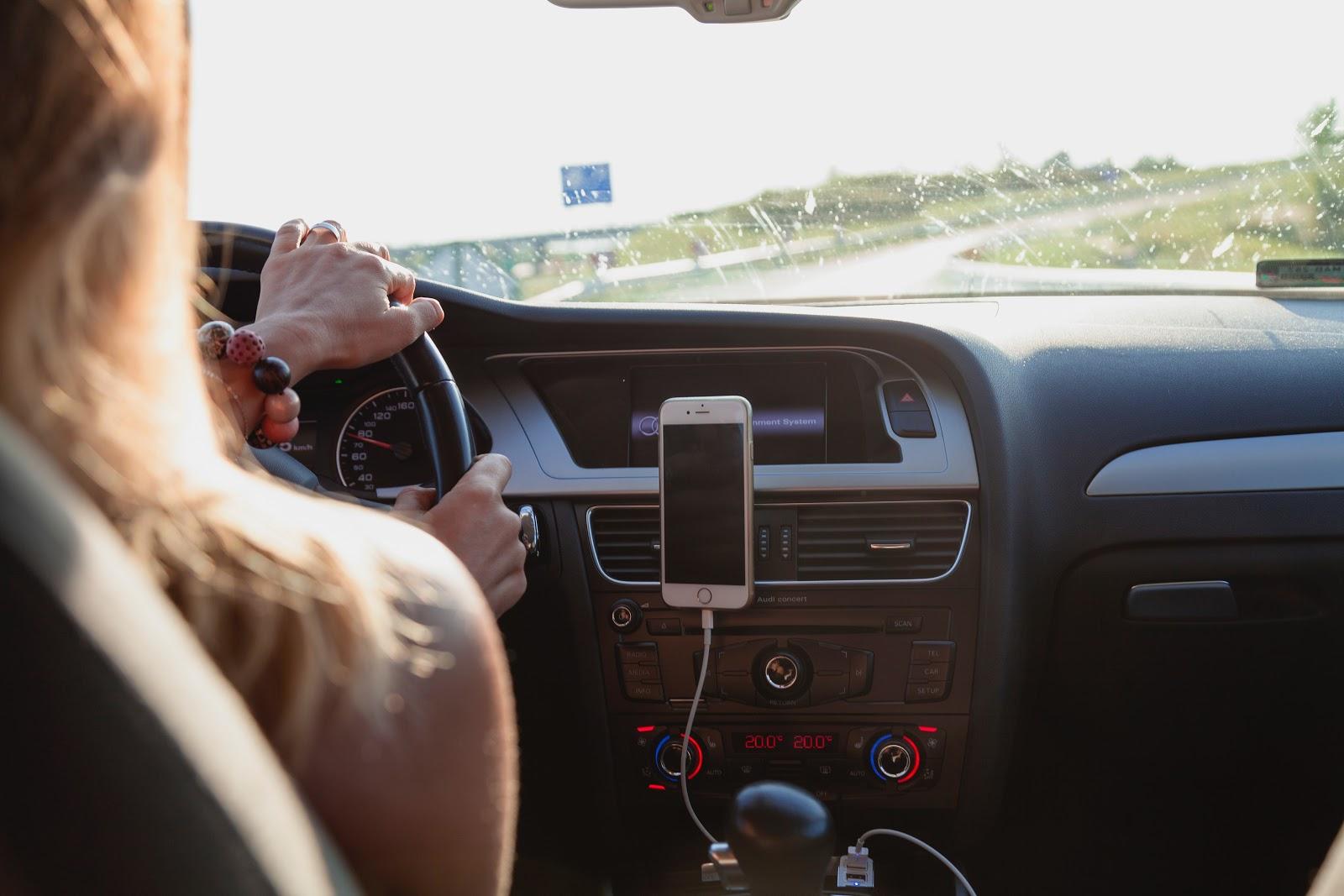 Mulher dirigindo o seu automóvel na pista
