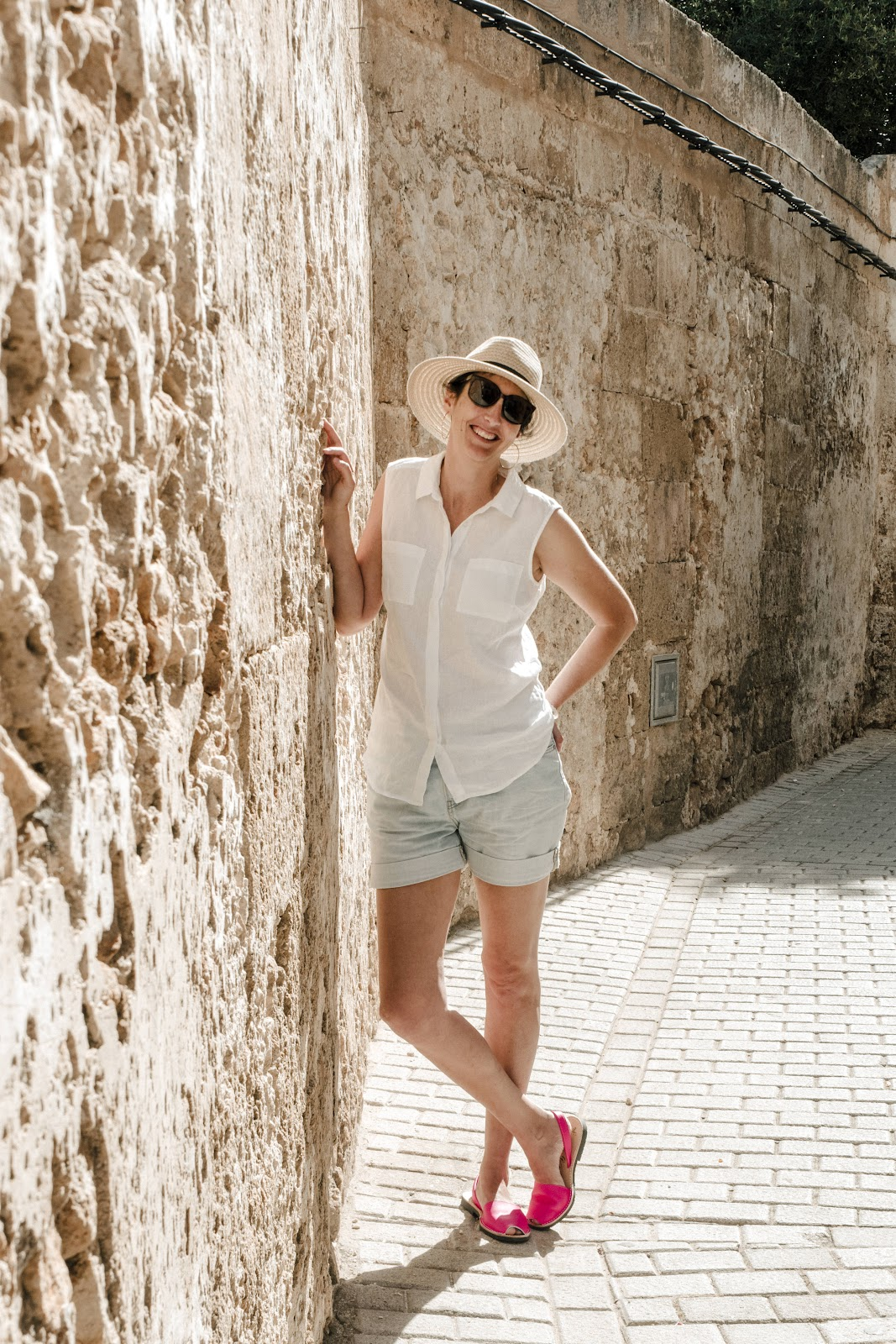 Owner Naomi leaning against a rock wall in Menorca wearing Neon Pink Avarcas