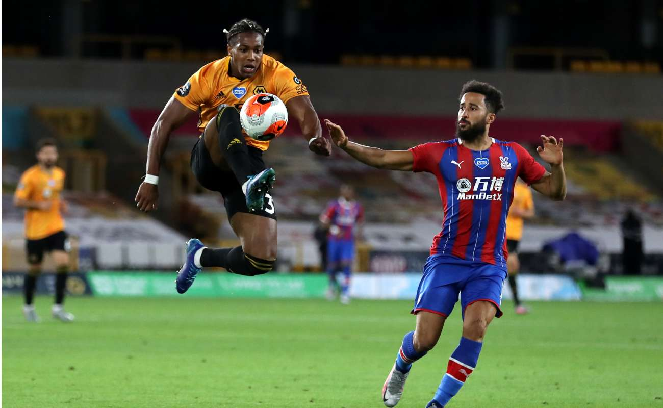 Wolves forward Adama Traoré jumps to win a ball in front of Andros Townsend of Crystal Palace