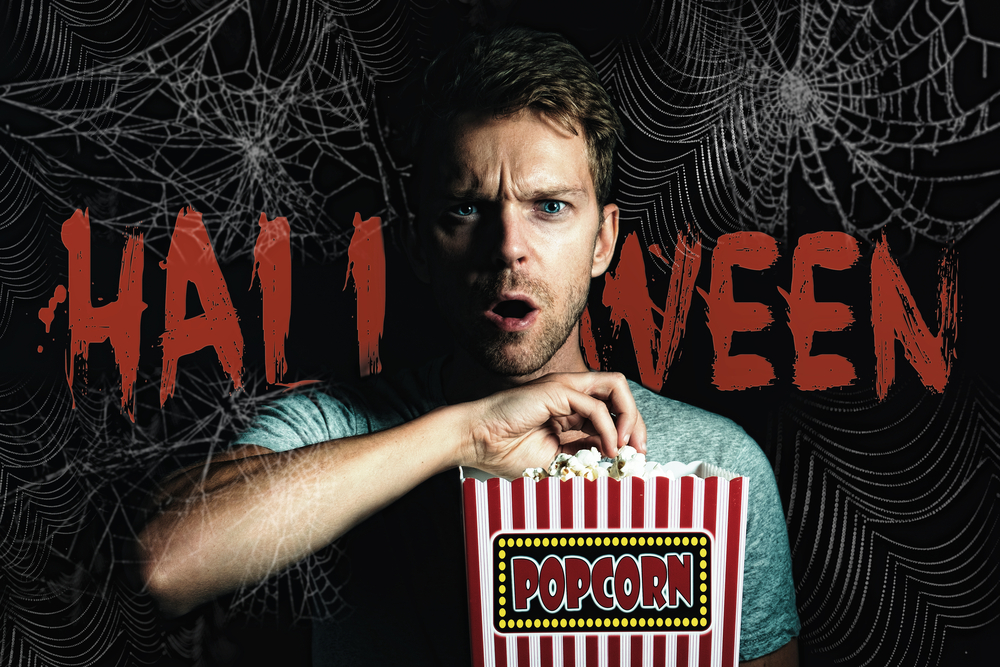 spiderweb on black background with the word Halloween in orange superimposed over it and a man eating popcorn with a terror stricken look on his face