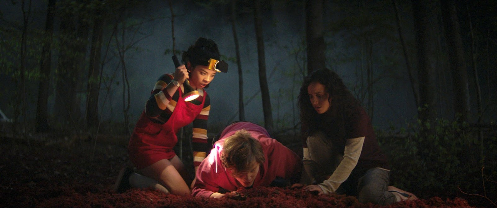 From left, Rehwald as Kate, Fred Hechnger as Simon and Madeira as Deena. They are crouching in a dark forest: Kate holding a large flashlight. Courtesy of Netflix.