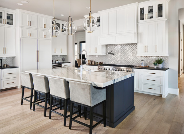 white shaker kitchen with paneled appliances, large center island, brass cabinet hardware, wood floors and glossy herringbone tile backsplash