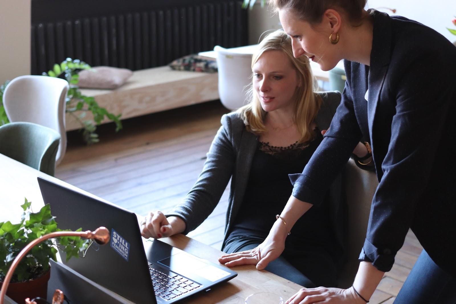 Uma mulher mostrando algo no computador para outra mulher.