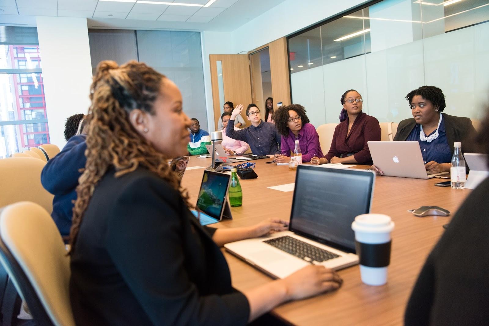 Várias pessoas sentadas em uma mesa de reunião.
