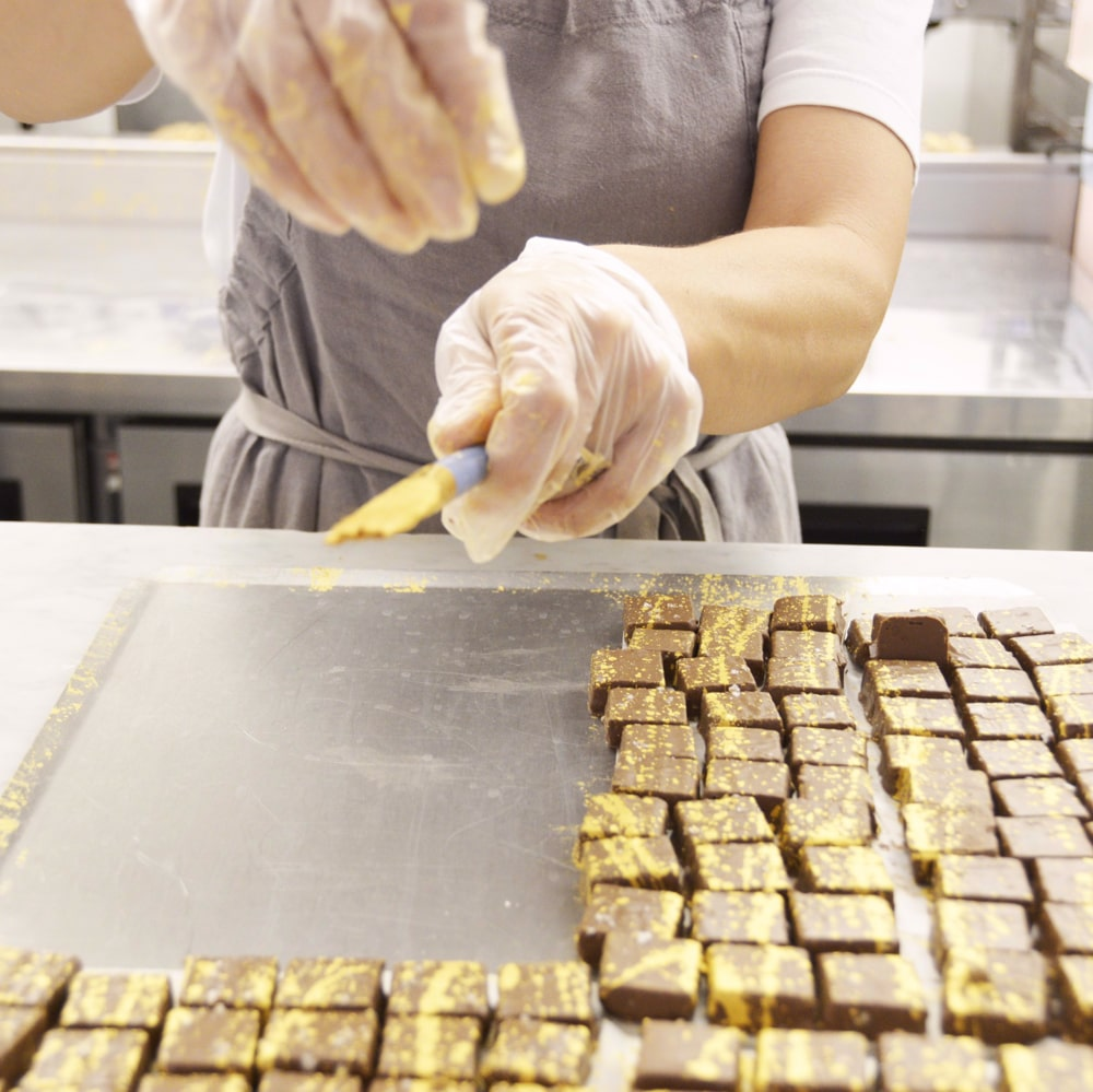 Homemade praline recipe; a person decorating pralines with a cooking brush