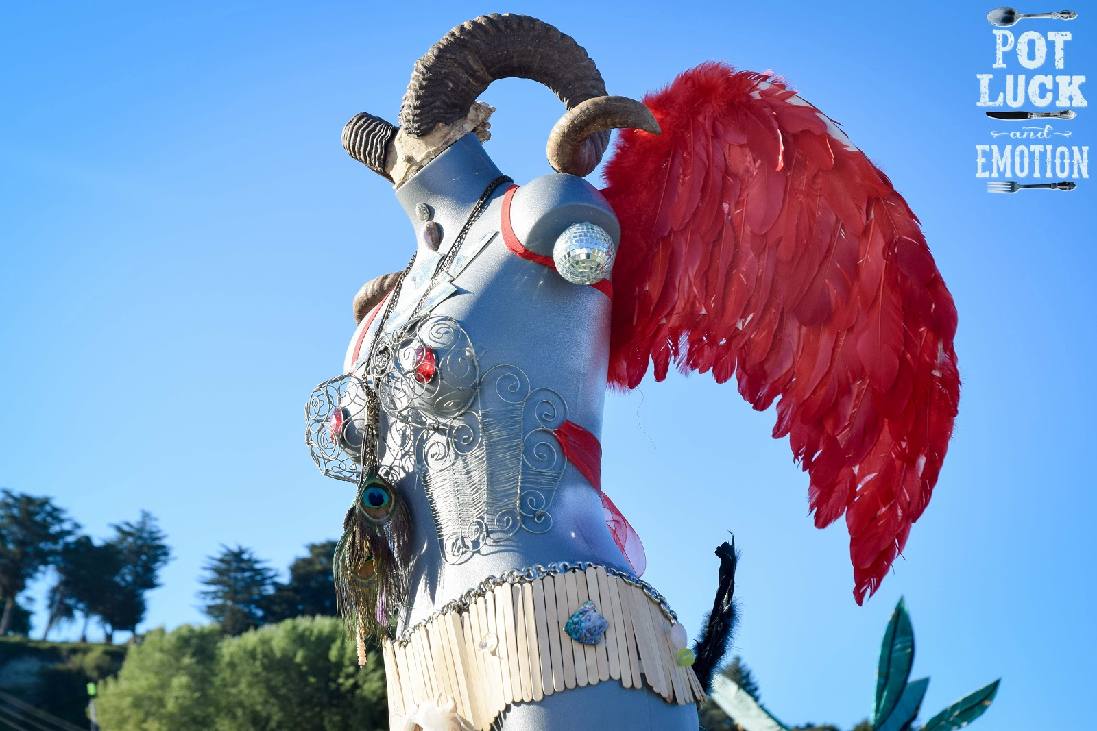 An art piece that is a woman's bodice dressed with feathers, goat horns, and metal adornment.