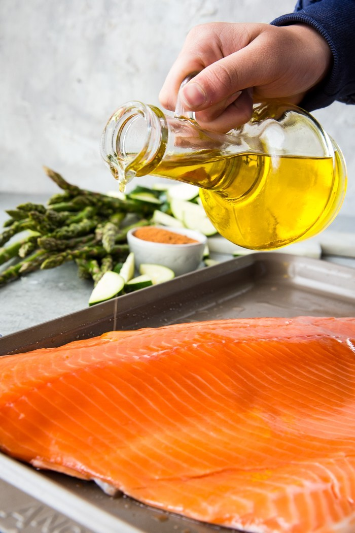 Pouring olive oil over a coho salmon fillet