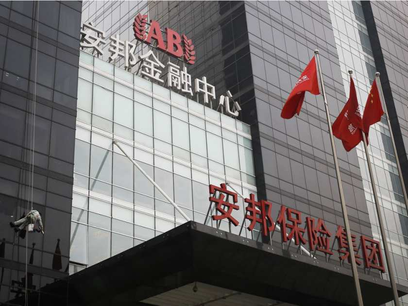 A worker cleans windows of the Anbang Insurance Group's building in Beijing, China.