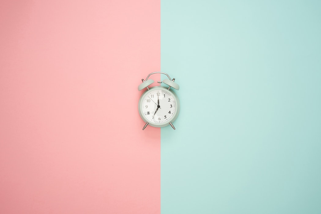 clock on the median of a pink and blue wall the thief of time procrastination