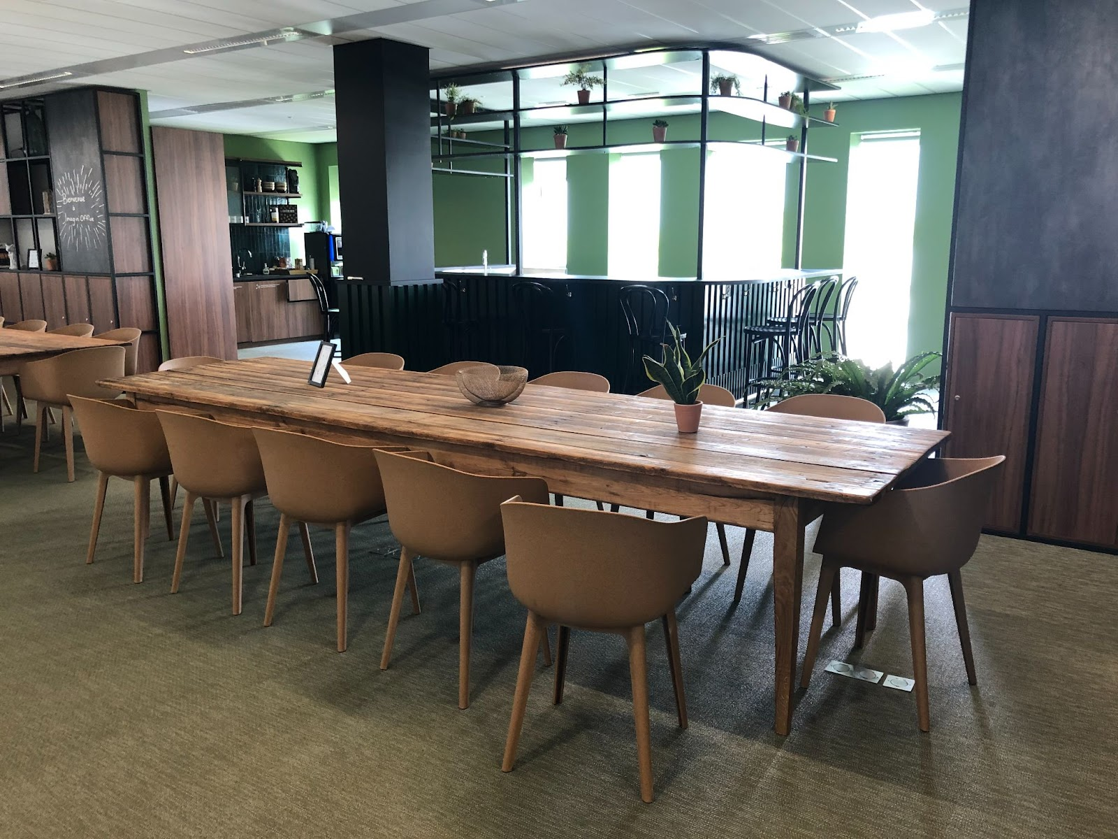 espace cafétéria entreprise avec tables conviviales en bois et espace bar