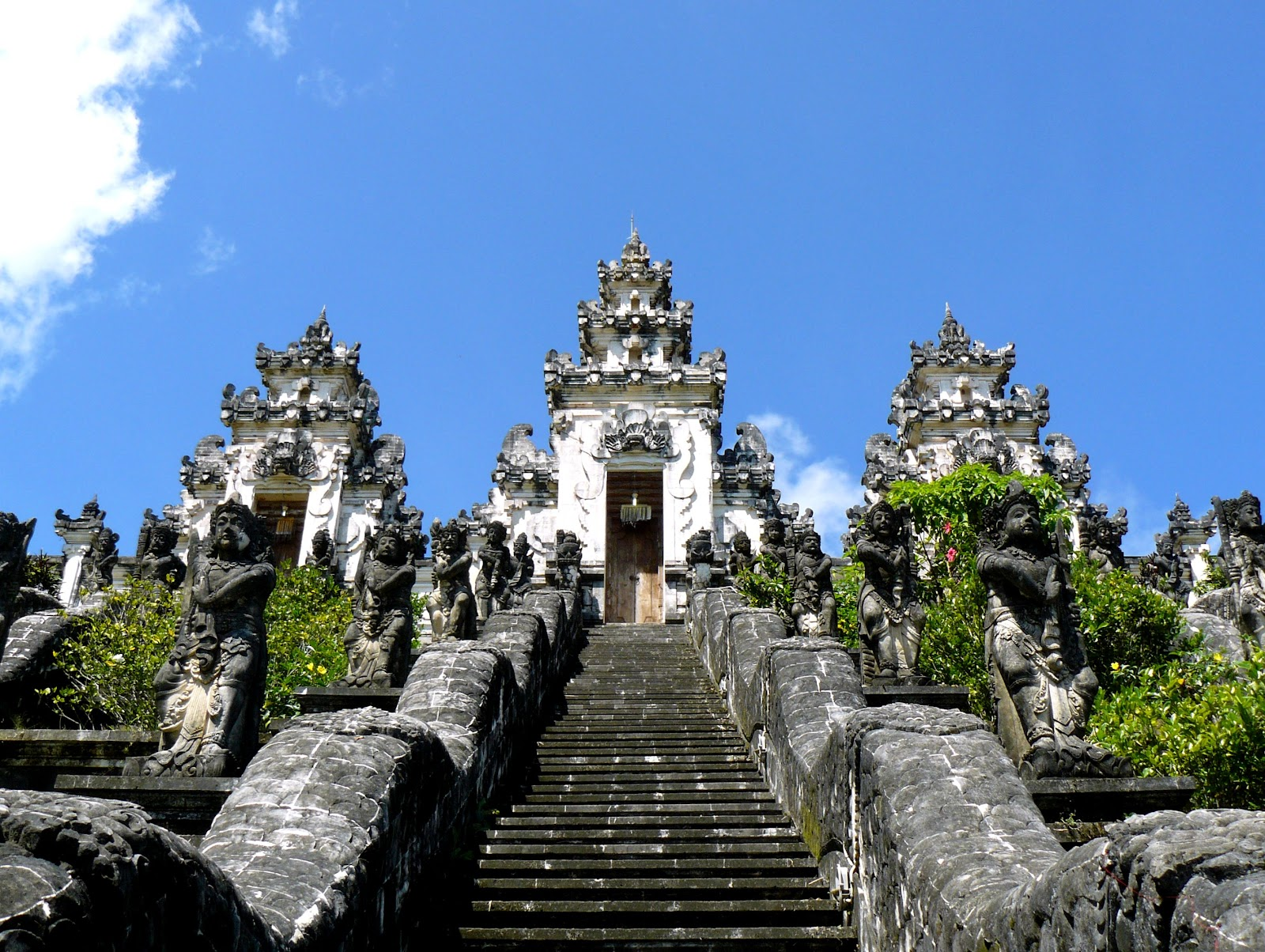 candi dasa buddhist temple whitewashed stone architecture traditional balinese statues and stairs on sunny day bali indonesia