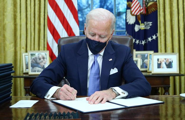President Joe Biden signs executive orders in the Oval Office of the White House. REUTERS/Tom Brenner