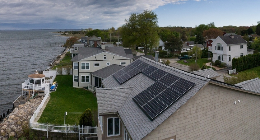 a waterfront home with solar panels on the roof
