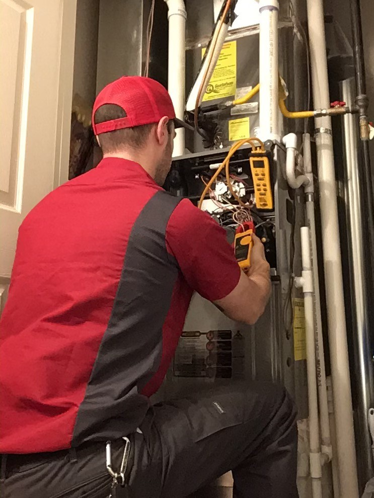 HVAC tech in a red and grey shirt kneels to perform diagnostics on an air handler before upgrading indoor air quality system