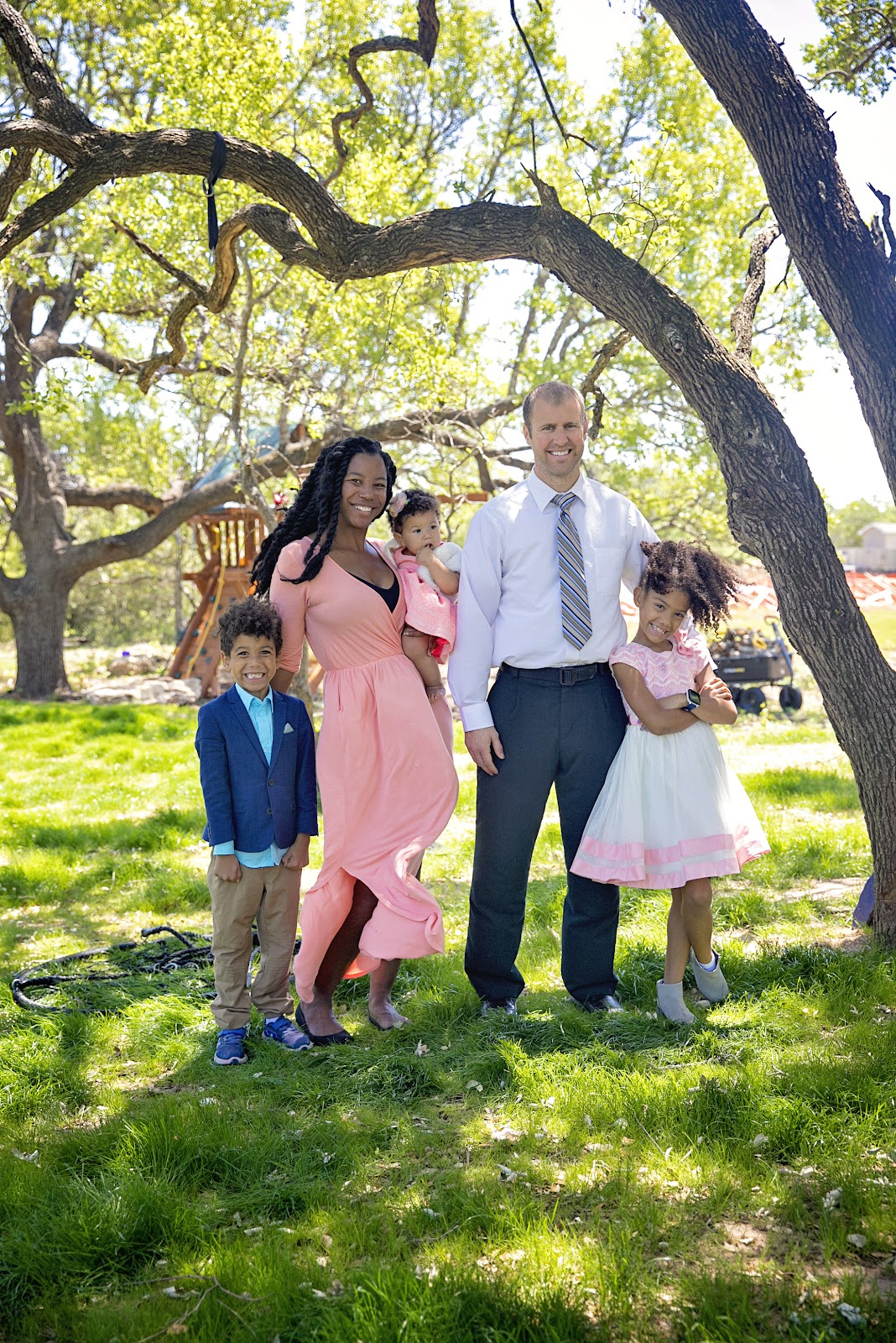 Interracial family standing in yard. Sharing the goal to pay off home in 5 years.