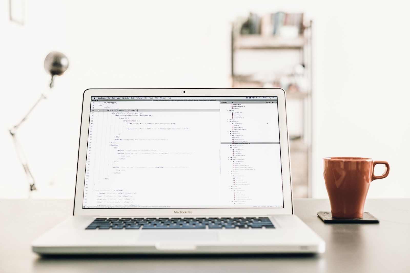 MacBook Pro on a desk with code written on it