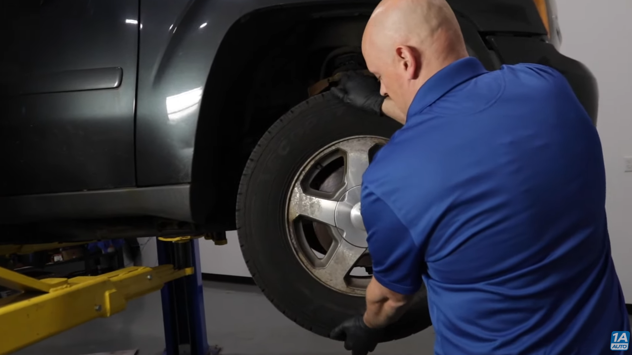 Testing the condition of a wheel bearing by holding and pressing the tire in and out from the 12 and 6 o'clock position
