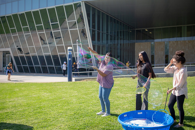 Students making bubbles in Bronco Commons
