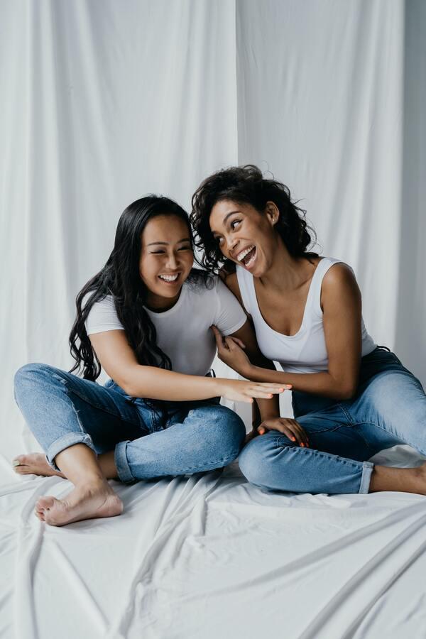 Duas amigas sentadas na cama rindo e descontraídas