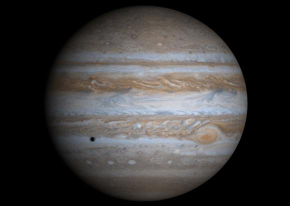 A true-color image of Jupiter taken by the Cassini spacecraft. The Galilean moon Europa casts a shadow on the planet's cloud tops. Credit: NASA/JPL/University of Arizona