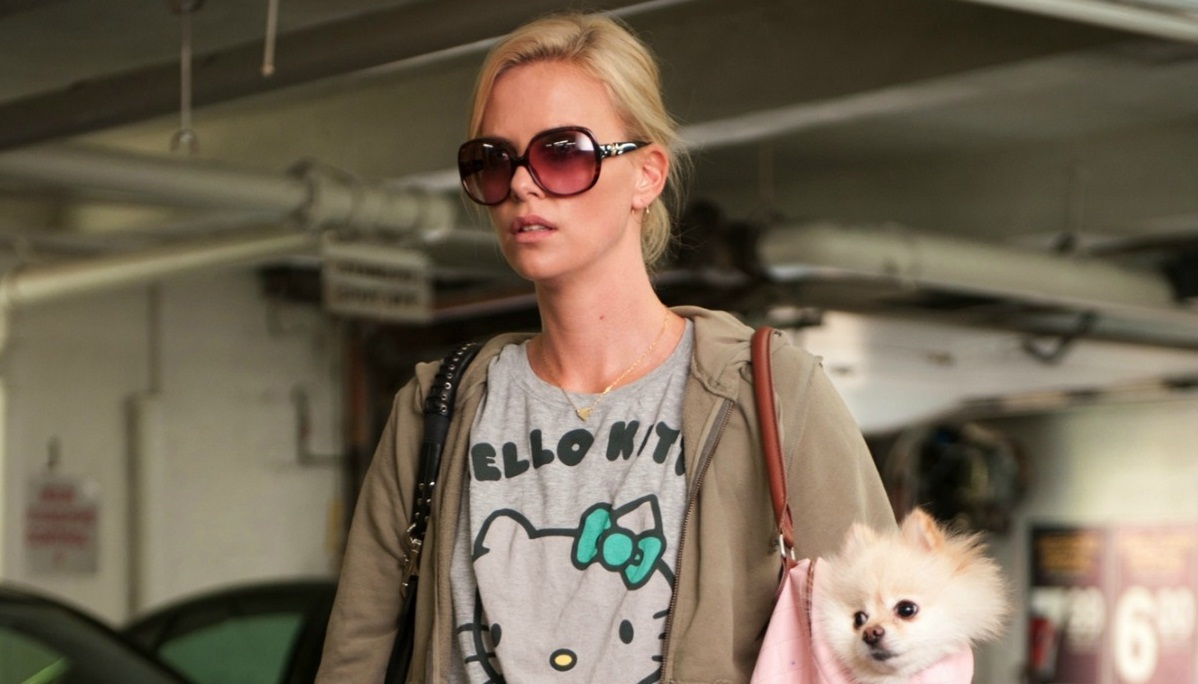Mavis, wearing a hello kitty shirt and large sunglasses, has a handbag slung over her shoulder with a small pomeranian dog in it. Her expression is one of displeasure.