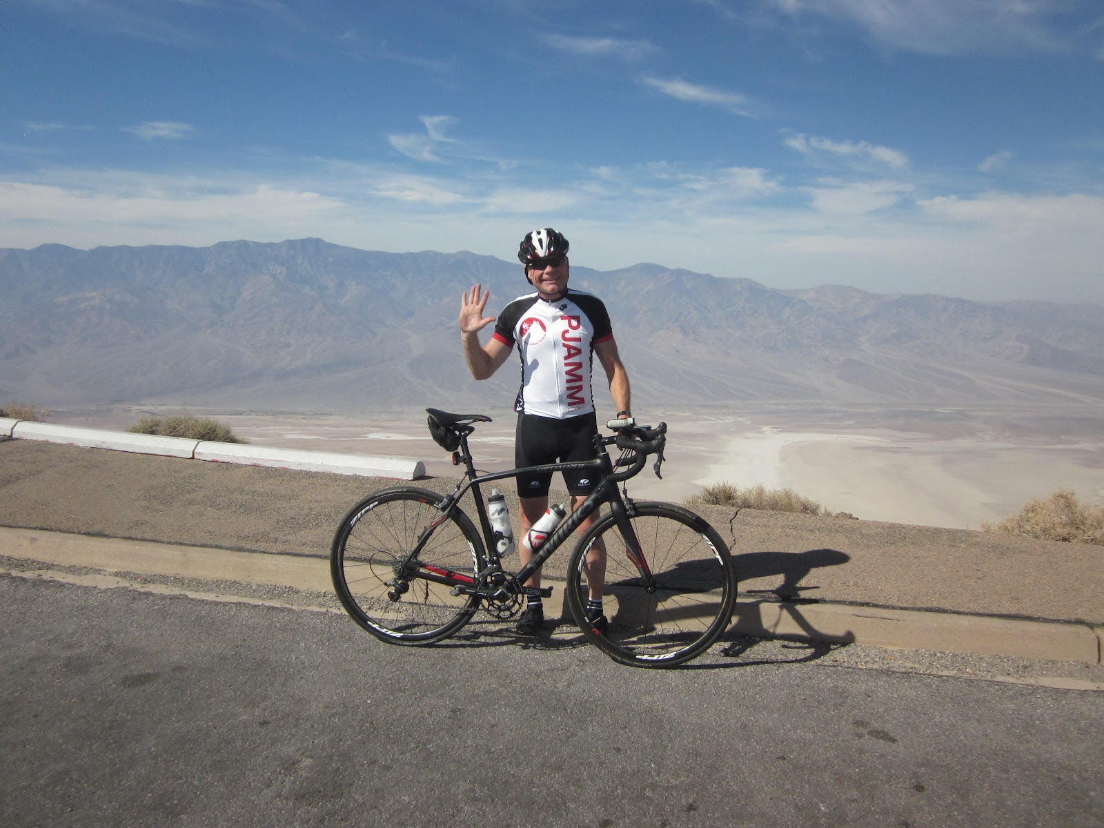 Climbing by bike Dantes View Death Valley - cyclist at Dantes View with Badwater in background
