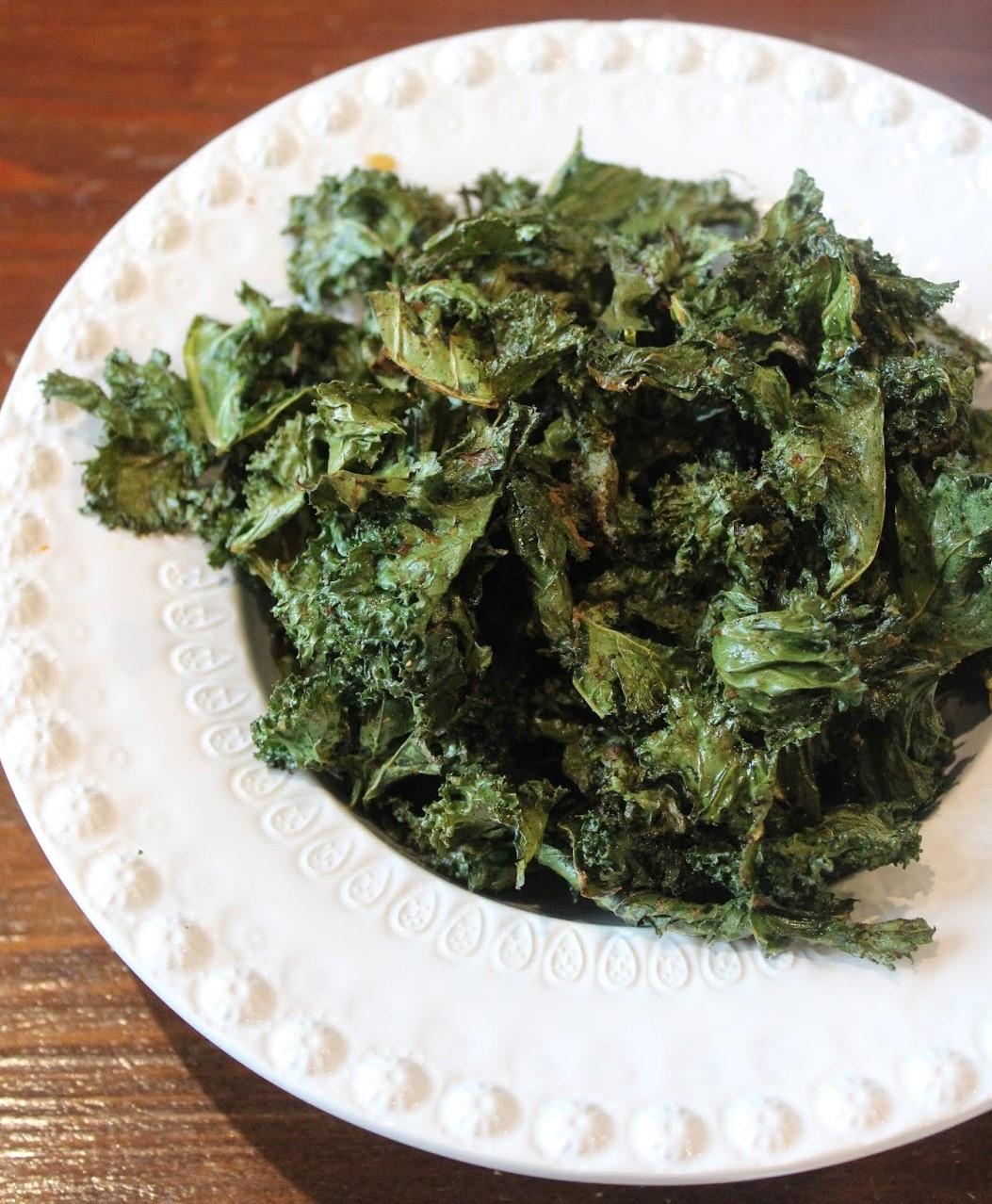 Couve crocante dentro de um prato branco fundo. Após assada, a couve diminui de volume e adquire um verde mais escuro que a sua cor quando está fresca.