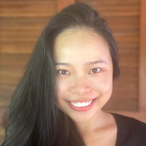 Mulher chinesa sorrindo para a câmera com os cabelos pretos e soltos.