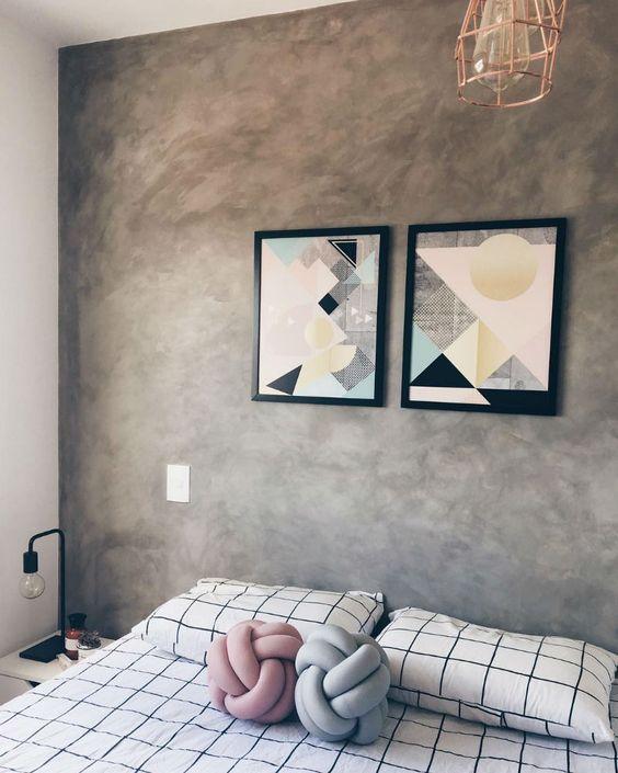 Quarto em estilo industrial com cama de casal e parede revestida de cimento queimado substituindo cabeceira