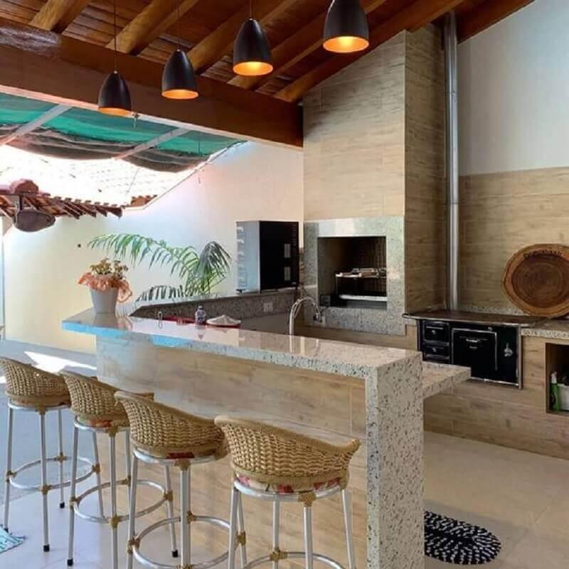 Área externa em estilo rústico contemporâneo com revestimento da churrasqueira e das bancadas, porcelanato que reproduz madeira e granito com bancos imitando palha e piso branco.