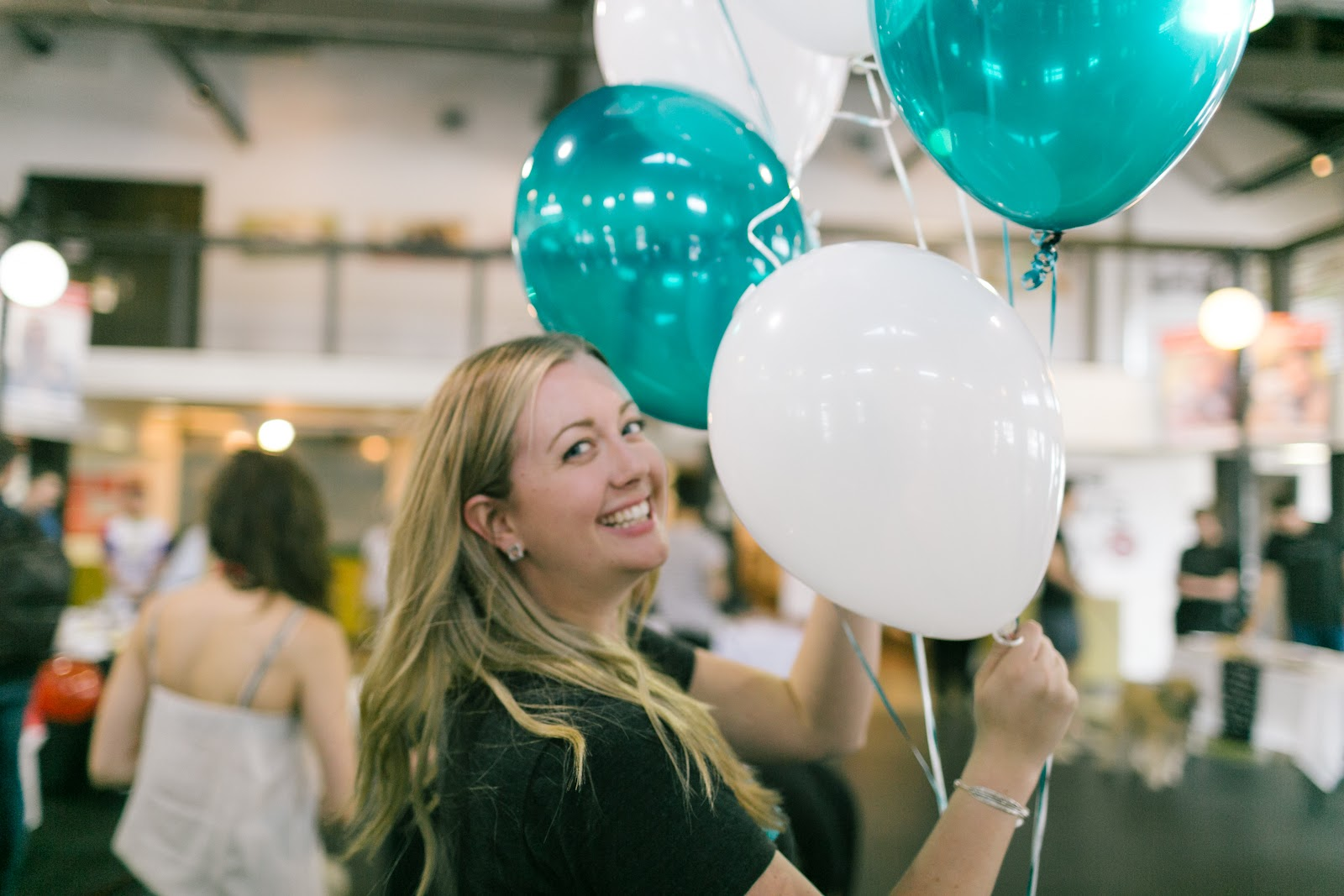 Woman smiling holding balloons.