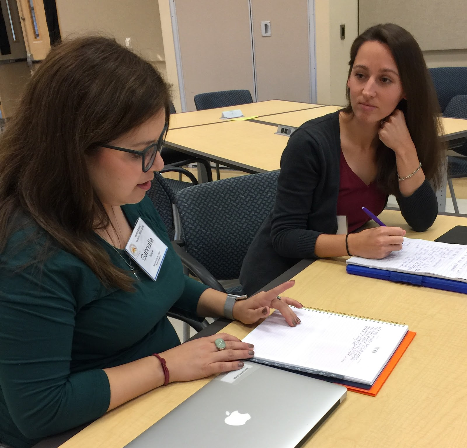 Two teachers sit at a table and talk to each other and take notes in notebooks.  They are seated in the TSBVI Outreach conference room.