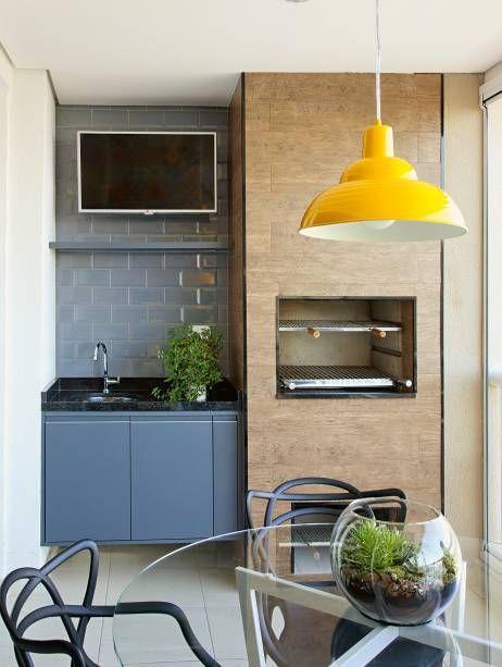 Cozinha gourmet com subway tiles azul na parede da pia harmonizando com armário azul e pia de granito preto, churrasqueira com revestimento amadeirado, piso branco, luminária pendente amarela e mesa de vidro redonda.