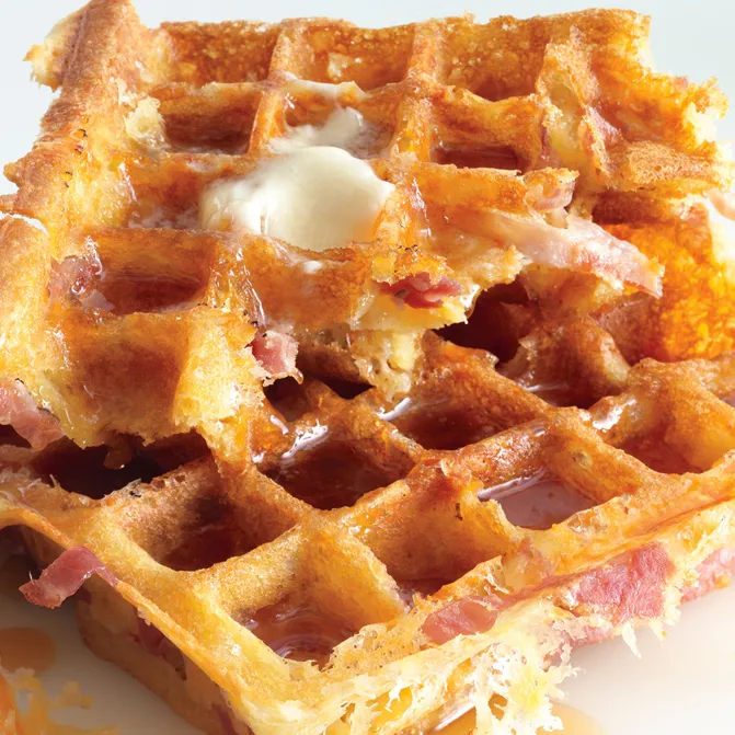 Golden brown waffles made with ham and cheese drizzled with maple syrup.