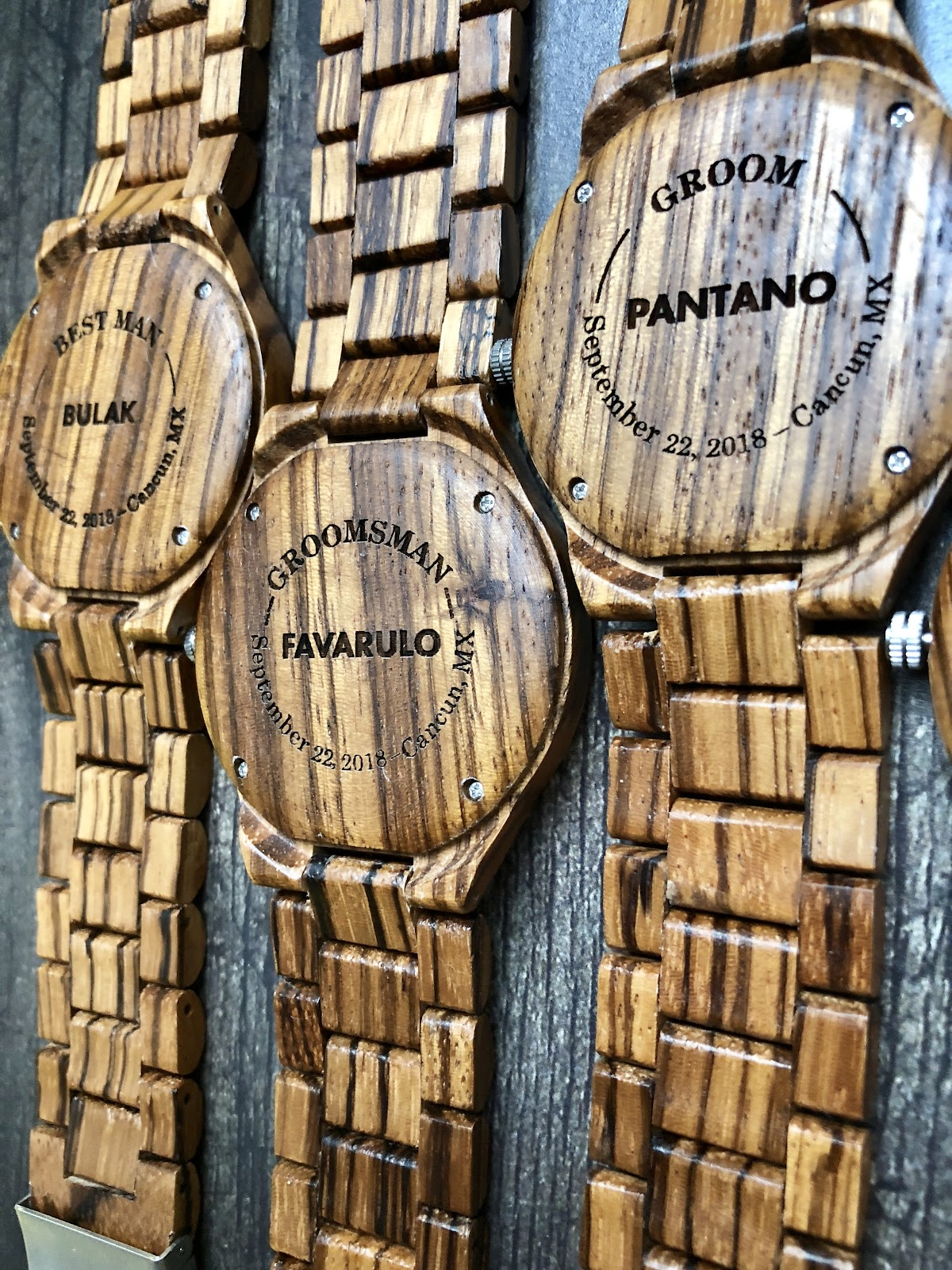 Wooden watches engraved with last name in the middle and surrounded by title, date and location.