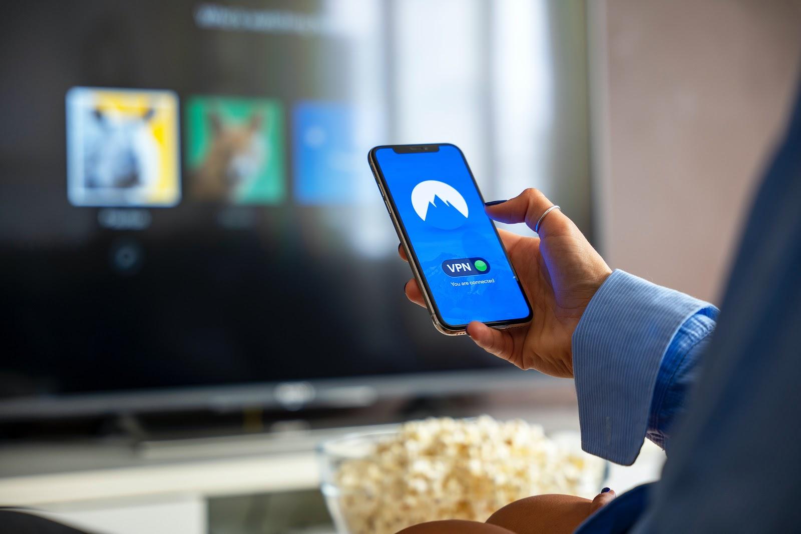 Mujer sujetando un teléfono donde se ve el VPN activado.