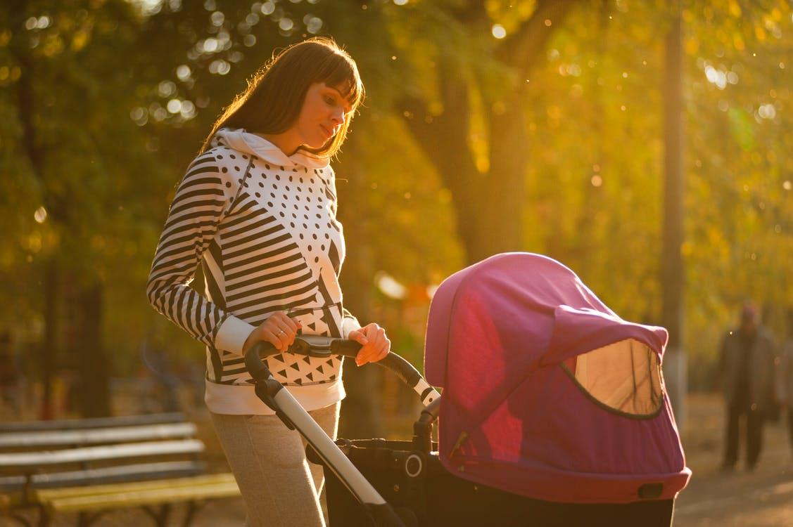 Woman Holding Pink And Black Stroller, Let's go, baby!