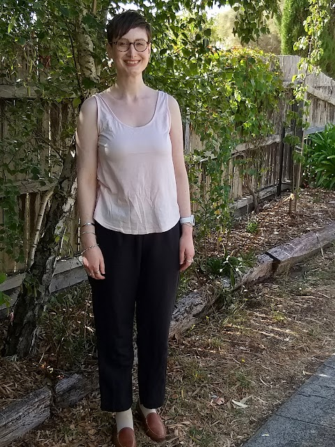Siobhan stands in front of a tree-lined fence. She wears a pink tank top, black elastic waist straight leg linen pants and brown loafers. She is smiling.