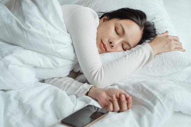 The woman is sleeping in the bed with her cellphone