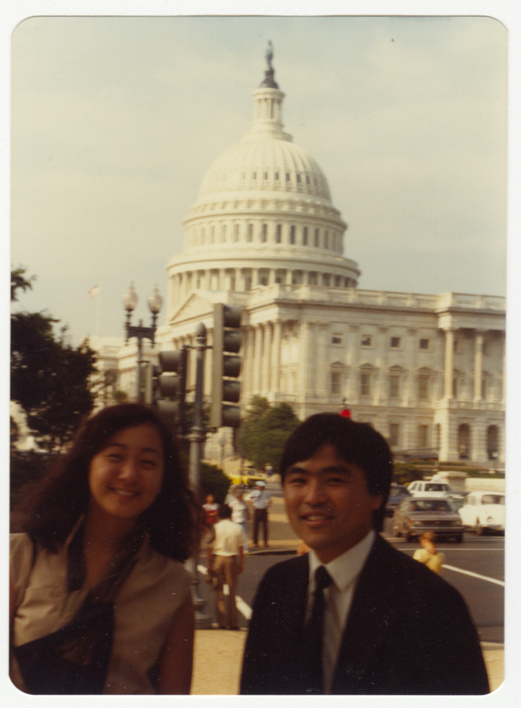 A young woman and young man posing across the street from the Capitol building in Washington, D.C.