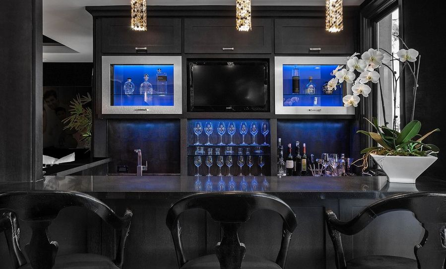 dark basement bar with blue cabinet lighting, dark grey cabinets and black accents