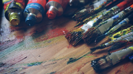 Pictured: Tubes of opened acryclic paint and some artist's paintbrushes splattered with various clolors.